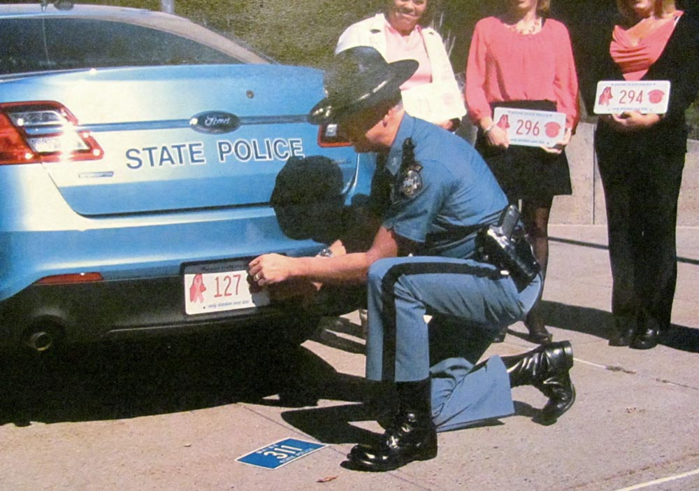 Maine police officer changing license plate on police car